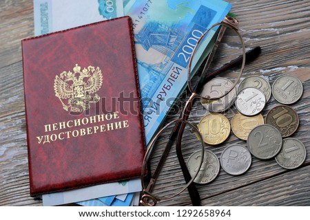 Russian money and a pension certificate and glasses . Russian translation: Pension Fund of the Russian Federation. Pensioner's ID on the wooden background, concept of pension reform, selective focus #1292658964