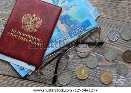 Russian money and a pension certificate and glasses . Russian translation: Pension Fund of the Russian Federation. Pensioner's ID on the wooden background, concept of pension reform, selective focus #1296441277