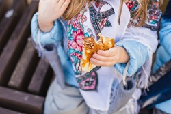 Russian national festival Maslenitsa, shrovetide. Little cute beautiful European girl in headscarf eat big tasty pancakes and have fun on winter pancake week. Traditional folf slavic street carnival.