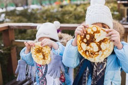 Russian national festival Maslenitsa, shrovetide. Little cute beautiful European girls in headscarf eat big tasty pancakes and have fun on winter pancake week. Traditional folf slavic street carnival.