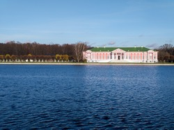 Russian noble estate on a sunny autumn day. The building of the eighteenth century, the church, the pavilion on the shore of a large pond. Well-groomed park with trimmed trees.
