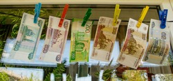 Russian paper banknotes of fifty, one hundred, two hundred, five hundred and one thousand rubles are attached with a clothespin to a clothesline for drying clothes