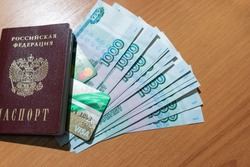 Russian paper money, as well as plastic cards and a Russian passport are located on a wooden table.