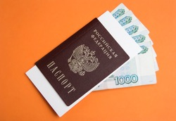 Russian passport with 1000 rubles money on an orange background with a place for the text. Inscription in Russian: Passport, Russian Federation, 1000 rubles.