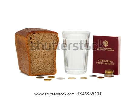 Russian pension certificate and glass of water with bread, cash rubles isolated on a white background. Translation text from Russian into English: pension fund Russian Federation. Pension certificate.