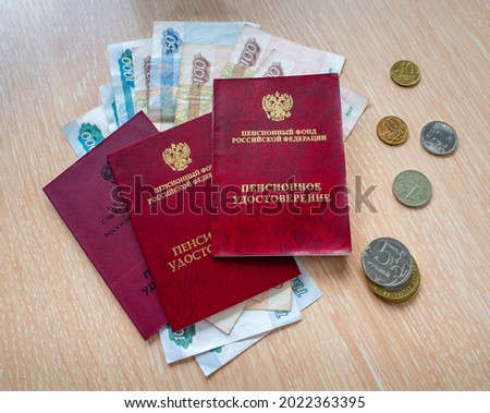 Russian pension certificates are stacked on top of each other. Paper and metal rubles are under documents and next to them.