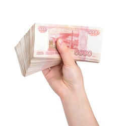 Russian rouble. Thick pack of five-thousand bills in a female right hand isolated on a white background.