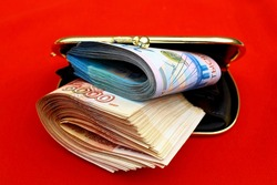 Russian rubles bills in a red open wallet. The denomination of the banknotes is two 2000 and five 5000 thousand rubles.