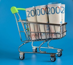 Russian rubles in a trolley on a blue background. Grocery basket and Russian rubles. Russian currency. Side view. Selective focus. Copy space