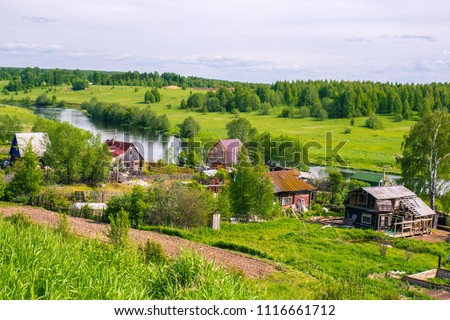 Russian rural landscape in summer, village houses on the river bank in greenery