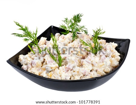 Russian salad in a black plate on a white background