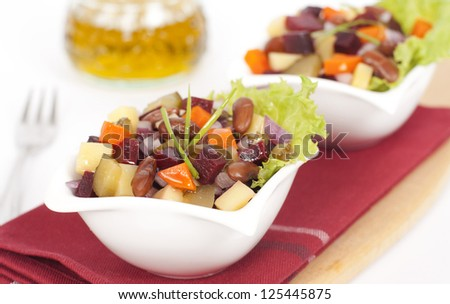 Russian salad vinaigrette served in two small plates on a dark red fabric