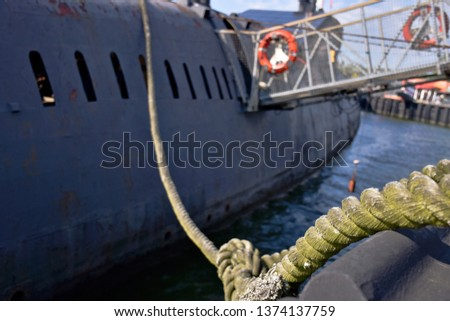 Russian submarine from the cold war. Picture from a harbor of the Baltic Sea. Rope in foreground.