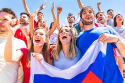 Russian supporters celebrating at stadium with flags. Group of fans watching a match and cheering team Russia. Sport and lifestyle concepts.