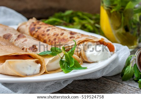 Russian thin pancakes with butter, cheese, jam, mint on a napkin on a wooden background.  Love for a healthy sweet  food concept