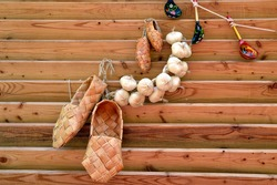 Russian traditional ancient bast shoes with bunch of garlic and rope with hunging wooden spoons. Composition in Russian Slavic style.