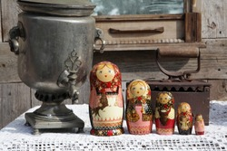 Russian traditional wooden nested dolls, matryoshka, in form of women in national costumes. Ancient iron, antique silver samovar for tea drinking. Russian style in folk art, handicraft, ethnic craft