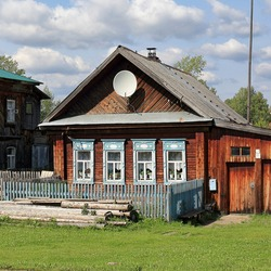 Russian village in summer. View of the old traditional wooden house with carved windows and wooden fence in front of it. Village of Visim, Sverdlovsk oblast, Urals, Russia.