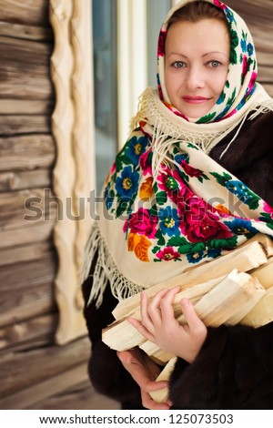Russian woman in a shawl carries firewood