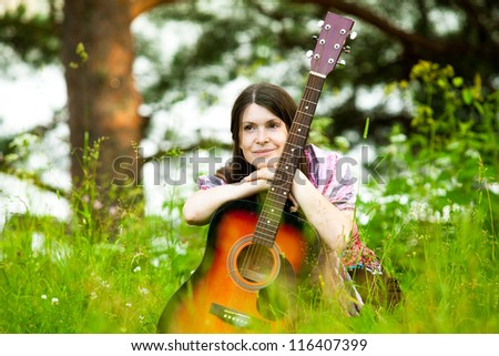 Russian woman with guitar in park