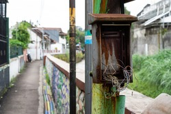 Rust and broken electrical cable box cabinet on metal power line pole.
