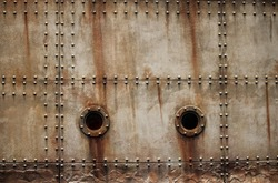 RUST AND TEXTURE ON METAL PLATE SIDES OF STAGED SHIPWRECK WITH RIVETS AND PORTHOLES