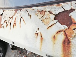 Rust has formed on the iron of an abandoned car body. Rust is formed when iron or some alloys containing iron are exposed to oxygen and moisture for a long time.