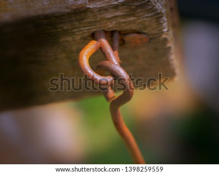 rust on a metal hook hooked to wood #1398259559