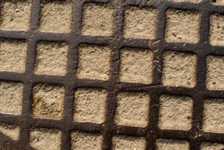 Rust steel grate with the sand inside the square. Inclined ancient lattice with the wet sand