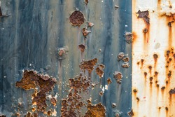 Rusted blue and white painted metal wall. Rusty metal background with streaks of rust