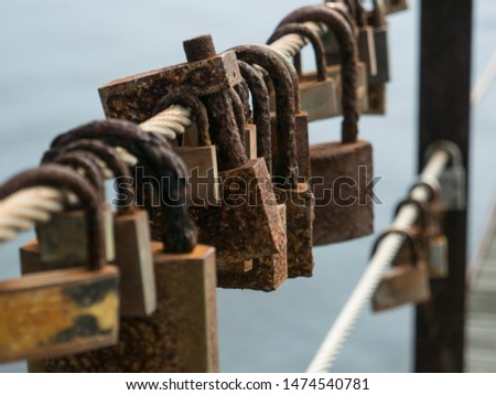 Rusted, corroded love locks / padlocks attached to a bridge. Shallow depth of field #1474540781