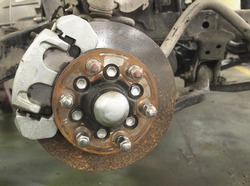 Rusted disc brake and caliper on car