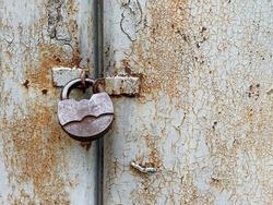 Rusted door with metal lock close up. Rusty metal background. Closed door with massive lock.
