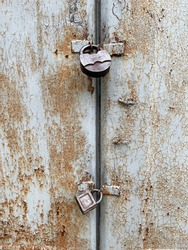 Rusted door with two metal locks. Rusty metal background. Closed door with massive locks.