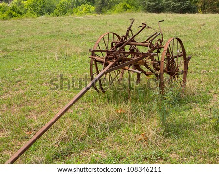 Rusted farm plow or plough pulled by horse in a field on farm - stock photo