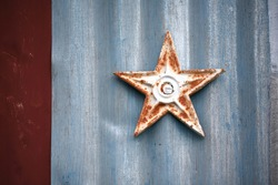 Rusted metal star on building