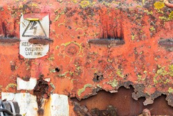 Rusted metal texture. Vintage machinery with warning sign, peeling paint and corroded metal, covered with yellow lichen