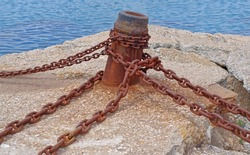 Rusted mooring bollard with chain on the berth