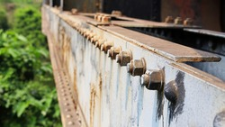 Rusted nuts and bolts on the old bridge. On the gray steel beam there are many anchor bolts which are part of the truss bridge with a copy area. Close focus and object selection