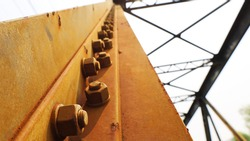 Rusted nuts and bolts on the old bridge. On the reddish-brown steel beam there are many anchor bolts which are part of the truss bridge and the shadow of the sun. Close focus and object selection