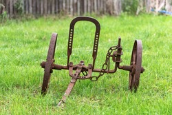 Rusted old metal plow. Soil treatment tool that works with the help of animals. An old rusty plow car in agriculture. Antique farm equipment