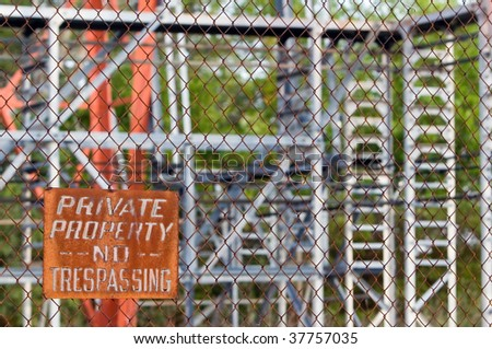 rusted sign on chain link fence