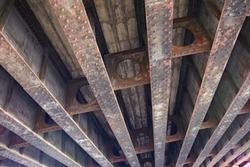 Rusted steel I beams of an old bridge closeup