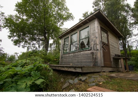 Rustic adorable homestead cabin with wall of windows overlooking the ocean in the Alaska woods on a misty overcast rainy day
