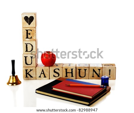 "Rustic alphabet blocks spelling out the message, ""Love Edukashun"" with a school bell, apple, and study supplies nearby.  Isolated on white."