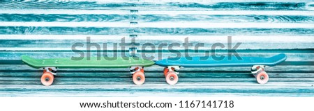 Rustic aqua blue and yellow green couple of used skateboards in love waiting together for their new young masters. Abstract children after school street activities and recreational sport background. #1167141718