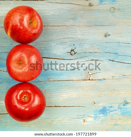 Rustic background three red apples on old blue wooden background