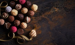 Rustic banner with luxury handmade chocolates and a heart shaped praline on a twirling gold ribbon over textured wood with vignette and copy space