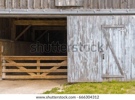 Rustic barn door open revealing animal stall and gate inside, peeling paint, hay on floor #666304312