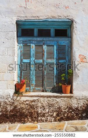 Rustic blue window and flower pots in Halki village, Naxos Island, Greece.